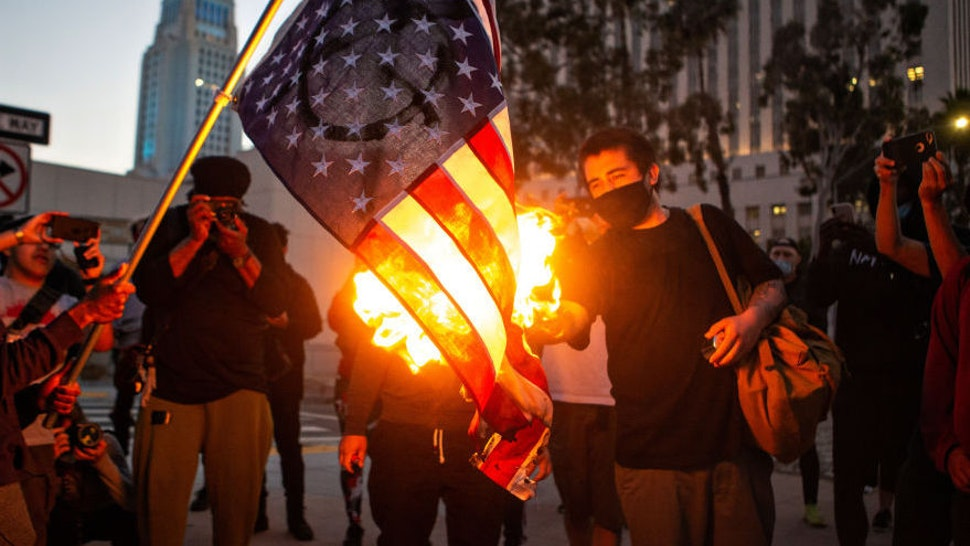 Los Angeles protester holds an American flag as a fellow demonstrator lights it on fire to protest the killing of George Floyd in Minnesota by police Wednesday, May 27, 2020 in Los Angeles, CA. (Jason Armond / Los Angeles Times)