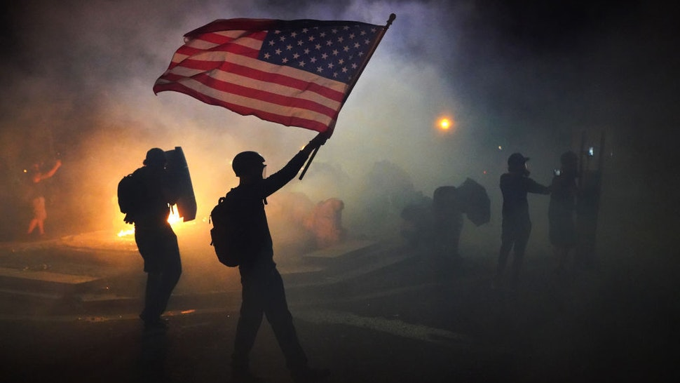 A protester flies an American flag while walking through tear gas fired by federal officers during a protest in front of the Mark O. Hatfield U.S. Courthouse on July 21, 2020 in Portland, Oregon. The federal police response to the ongoing protests against racial inequality has been criticized by city and state elected officials. (Photo by Nathan Howard/Getty Images)