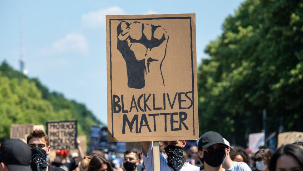 "27 June 2020, Berlin: During a ""Black Lives Matter"" demonstration at the Victory Column, a participant holds a poster with the words ""Black Lives Matter"". More than 1000 people demonstrated against racism on the Street of June 17. Photo: Christophe Gateau/dpa (Photo by Christophe Gateau/picture alliance via Getty Images)"