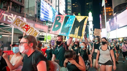 People wearing masks are seen protesting in Times Square as the city continues Phase 4 of re-opening following restrictions imposed to slow the spread of coronavirus on July 28, 2020 in New York City. The fourth phase allows outdoor arts and entertainment, sporting events without fans and media production. (Photo by Alexi Rosenfeld/Getty Images)