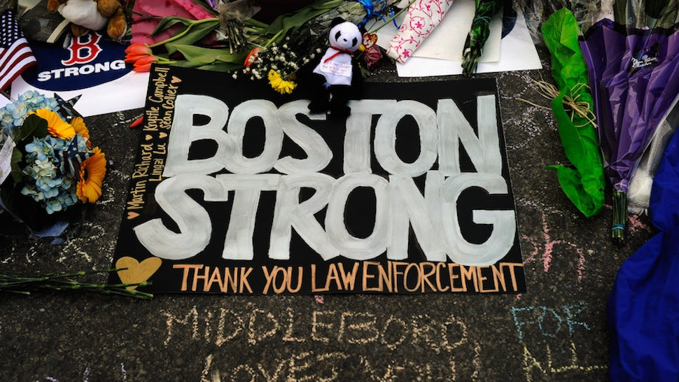 BOSTON, MA - APRIL 21: A large sign with the names of the Boston Marathon bombing victims and thanking law enforcement is placed by a Boston Bruins hockey team fan at a makeshift memorial for victims near the site of the bombings at the intersection of Boylston Street and Berkley Street two days after the second suspect was captured on April 21, 2013 in Boston,Massachusetts. A manhunt for Dzhokhar A. Tsarnaev, 19, a suspect in the Boston Marathon bombing ended after he was apprehended on a boat parked on a residential property in Watertown, Massachusetts. His brother Tamerlan Tsarnaev, 26, the other suspect, was shot and killed after a car chase and shootout with police. The bombing, on April 15 at the finish line of the marathon, killed three people and wounded at least 170. (Photo by Kevork Djansezian/Getty Images)
