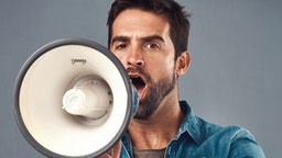 Studio shot of a handsome young man using a megaphone against a grey background