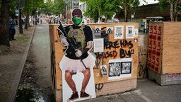 A cutout image of a man holding a firearm, called ANTI-FAiry and created by activists to critique the recent manipulation and misleading use of the mans image by Fox News, is seen at an entrance in the area known as the Capitol Hill Organized Protest (CHOP) on June 24, 2020 in Seattle, Washington. On Monday, Seattle Mayor Jenny Durkan said that the city would phase down the CHOP zone and that the Seattle Police Department would return to its vacated East Precinct. (Photo by David Ryder/Getty Images)
