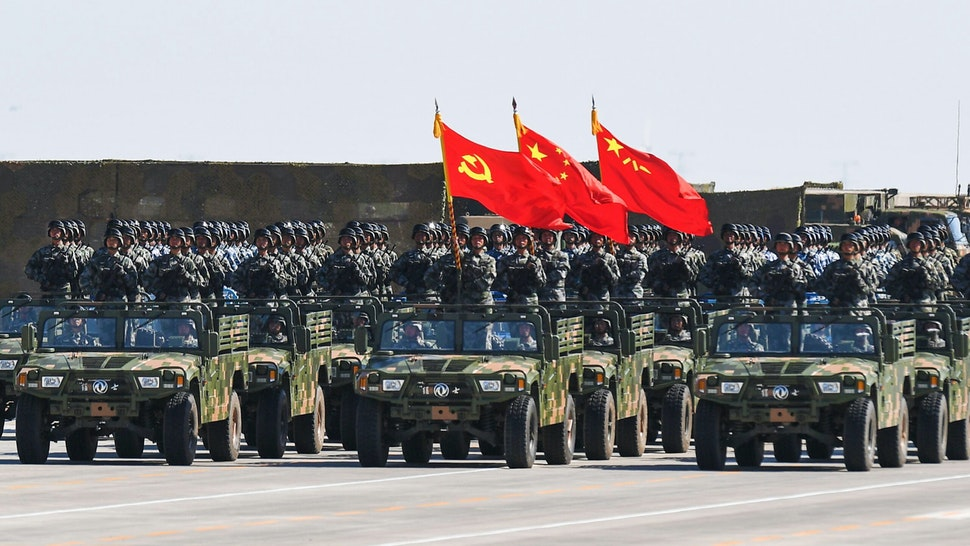 Chinese soldiers carry the flags of (L to R) the Communist Party, the state, and the People's Liberation Army during a military parade at the Zhurihe training base in China's northern Inner Mongolia region on July 30, 2017. China held a parade of its armed forces on July 30 to mark the 90th anniversary of the People's Liberation Army (PLA) in a display of military might.