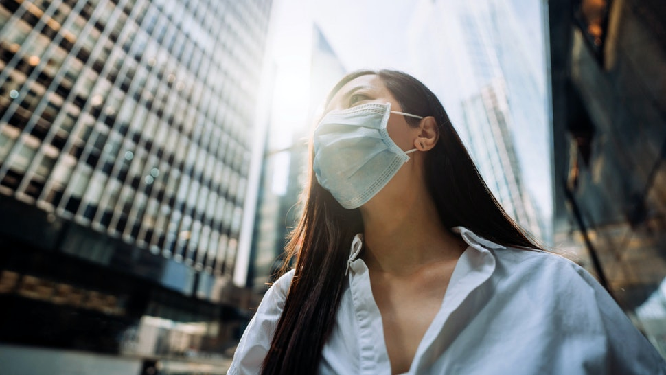 Young Asian businesswoman with protective face mask to protect and prevent from the spread of viruses during the coronavirus health crisis, standing in an energetic and prosperous downtown city street against corporate skyscrapers.