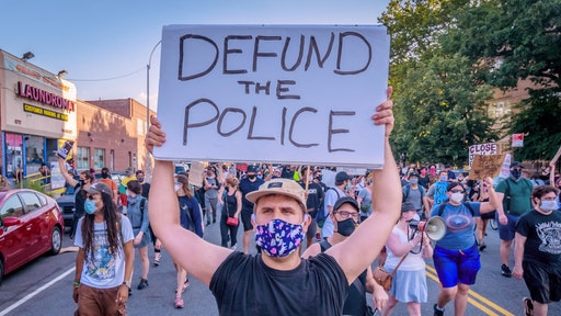 A counterprotester holding a Defund Police sign at the protest. Pro-NYPD marchers clashed with a big crowd of Black Lives Matter counterprotesters during the ìBack the Blueî rally and march in Bay Ridge, Brooklyn. (Photo by Erik McGregor/LightRocket via Getty Images)
