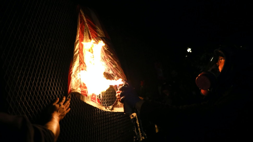 PORTLAND, OREGON - JULY 25: An American Flag is burned as protesters gather in front of the Mark O. Hatfield federal courthouse in downtown Portland as the city experiences another night of unrest on July 25, 2020 in Portland, Oregon. For over 55 straight nights, protesters in downtown Portland have faced off in often violent clashes with the Portland Police Bureau and, more recently, federal officers. The demonstrations began to honor the life of George Floyd and other black Americans killed by law enforcement and have intensified as the Trump administration called in the federal officers.