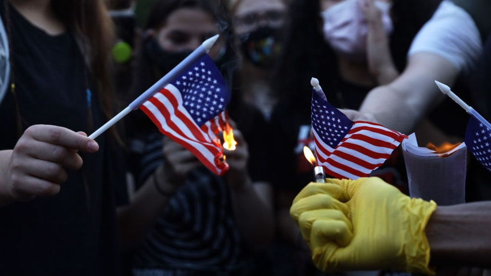 Anti-Trump activists burn U.S. flags at Black Lives Matter Plaza near the White House July 4, 2020 in Washington, DC. Anti-Trump activists rallied on Independence Day to voice their disapproval of President Trump's handling in the wake of the death of George Floyd. (Photo by Alex Wong/Getty Images)