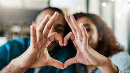Shot of a young couple making a heart gesture with their hands outdoors