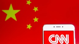 In this photo illustration the American news-based pay television channel CNN logo is seen on an Android mobile device with People's Republic of China flag in the background.