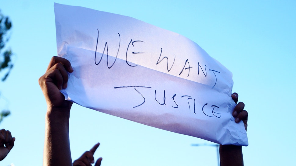 Low Angle View Of Person Holding Paper With Justice Text Against Sky - stock photo