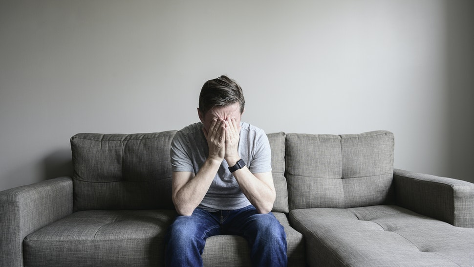 Depressed mature man sitting on couch - stock photo