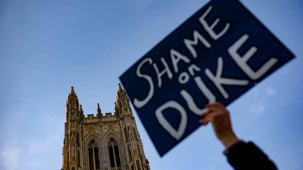 """Seth Lejaq, a first year writing teacher at Duke University, holds up a sign while protesters joined outside the venue where former National Security Advisor John Bolton will discuss the """"current threats to national security"""" during a forum moderated by Peter Feaver, the director of Duke's American Grand Strategy, at the Page Auditorium on the campus of Duke University on February 17, 2020 in Durham, North Carolina."""