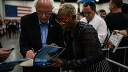 Former Ohio state Sen. Nina Turner holds a book for Sen. Bernie Sanders, I-Vt., 2020 Democratic Presidential Candidate to sign after speaking during a rally at the Myrtle Beach Convention Center on Wednesday, February 26, 2020 in Myrtle Beach, SC.