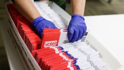 Election workers sort vote-by-mail ballots for the presidential primary at King County Elections in Renton, Washington on March 10, 2020.