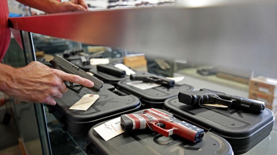 A worker restocks handguns at Davidson Defense in Orem, Utah on March 20, 2020.