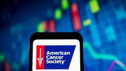 photo illustration an American Cancer Society logo seen displayed on a smartphone.