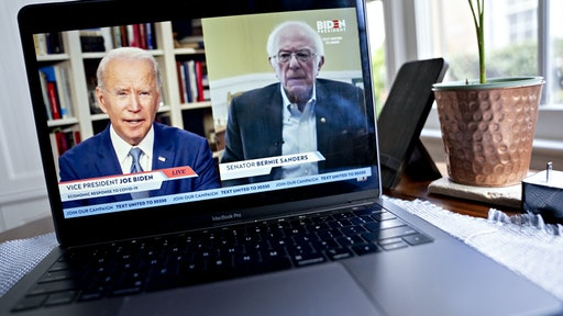 Former Vice President Joe Biden, presumptive Democratic presidential nominee, left, speaks as Senator Bernie Sanders, an Independent from Vermont, right, listens during a virtual event seen on an Apple Inc. laptop computer in Arlington, Virginia, U.S., on Monday, April 13, 2020. Sanders endorsed Biden during the joint livestream saying that Americans of all political affiliations should back the former vice president. Photographer: Andrew Harrer/Bloomberg via Getty Images