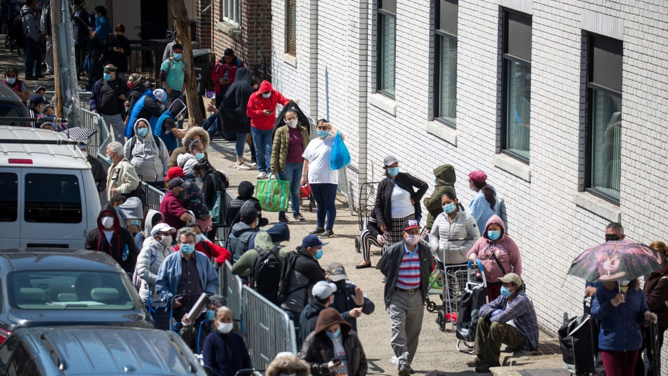 People wait to receive food at a food distribution site in the Brooklyn borough of New York, the United States, May 14, 2020.