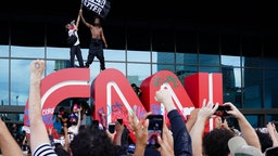 A man waves a Black Lives Matter flag atop the CNN logo during a protest in response to the police killing of George Floyd outside the CNN Center on May 29, 2020 in Atlanta, Georgia.