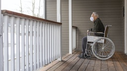 Senior man in wheelchair wearing protective mask to prevent coronavirus transmission on porch - stock photo