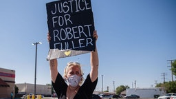 A protester holds up a placard on Palmdale Blvd as people gather to demand justice for Robert Fuller, a young black man who was found hanging from a tree, on June 16, 2020, in Palmdale, California.