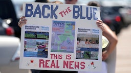 """A sign posts """"real news"""" and calls to """"back the blue"""" at a Back the Blue rally in support of police departments on Quincy Shore Drive in Quincy, MA on June 20, 2020."""