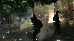 Tear gas and fireworks mix as Black Lives Matter supporters demonstrate in Portland, Oregon on July 4, 2020 for the thirty-eighth day in a row at Portland's Justice Center and throughout Portland,