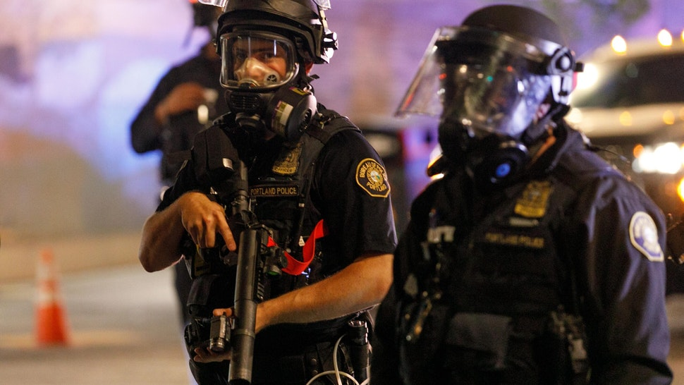 PORTLAND, OREGON, USA: Police confront demonstrators as Black Lives Matter supporters demonstrate in Portland, Oregon on July 4, 2020 for the thirty-eighth day in a row at Portland's Justice Center and throughout Portland, with a riot declared about 12.20 am on July 5. CS tear gas and less-lethal weapons were used, and multiple arrests were made. (Photo by John Rudoff/Anadolu Agency via Getty Images)