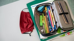 """08 July 2020, Baden-Wuerttemberg, Marbach am Neckar: A mouth-and-nose cover lies on a school desk next to a pencil case and school books during a lesson of a fifth grade of the Friedrich-Schiller Gymnasium. In Baden-Württemberg, the pupils will be given regular lessons again after the summer holidays - if the coronavirus allows it. (to dpa """"Eisenmann reveals plans for the schools"""") Photo: Marijan Murat/dpa (Photo by Marijan Murat/picture alliance via Getty Images)"""