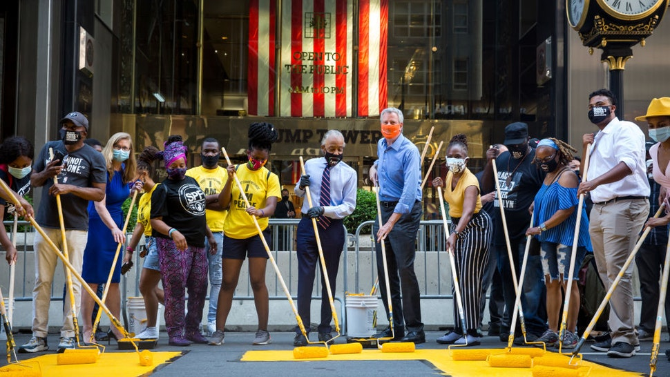 Bill de Blasio, mayor of New York, center right, and Reverend Al Sharpton, president and founder of the National Action Network Inc. (NAN), center, paint a 'Black Lives Matter' mural along Fifth Avenue in front of Trump Tower in New York, U.S., on Thursday, July 9, 2020.