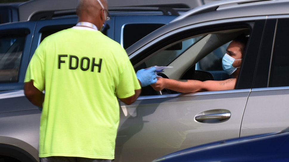A health department worker checks in a man wearing a mask to be tested for COVID-19 at a drive through testing site at Osceola Heritage Park.