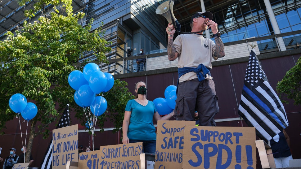 A former law enforement officer leads a chant during a Rally to Support Seattle Police Department rally in front of City Hall on July 15, 2020 in Seattle, Washington.