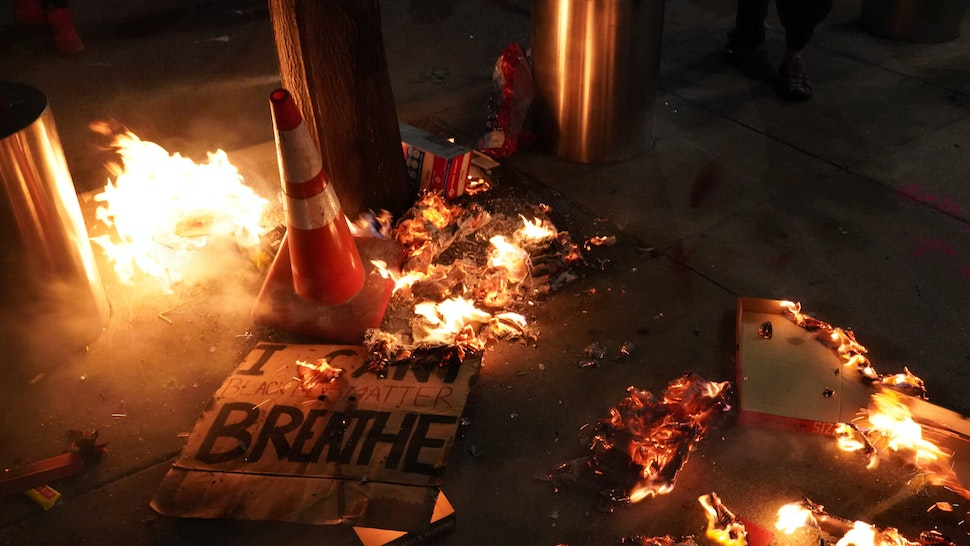 PORTLAND, OR - JULY 20: A fire burns around a sign reading I cant breathe during a protest in front of the Mark O. Hatfield U.S. Courthouse on July 201, 2020 in Portland, Oregon. Monday night marked 54 days of protests in Portland following the death of George Floyd in police custody. (Photo by Nathan Howard/Getty Images)