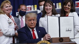 U.S. President Donald Trump holds an executive order on lowering drug prices after being signed during a ceremony in the Eisenhower Executive Office Building in Washington, D.C., U.S., on Friday, July 24, 2020.