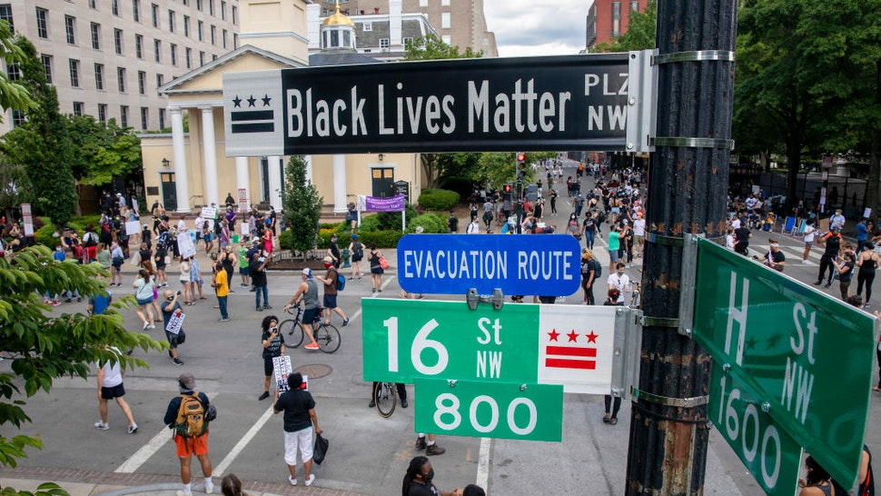 """People walk near 16th and H street after volunteers, with permission from the city, painted """"Black Lives Matter"""" on the street near the White House on June 05, 2020 in Washington, DC."""