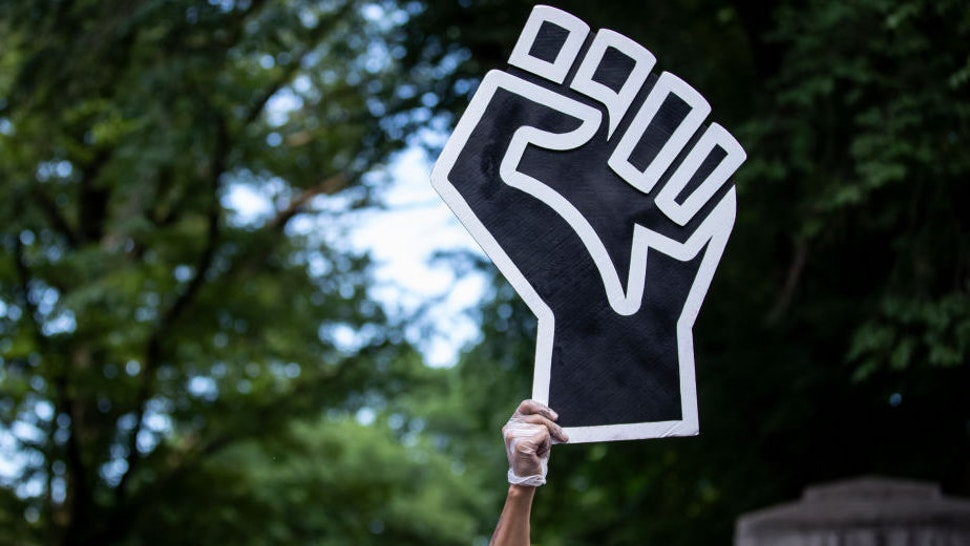A protester wearing a mask holds a large black power raised fist in the middle of the crowd that gathered at Columbus Circle.
