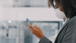 Shot of a young businesswoman wearing a mask and using a smartphone in a modern officeShot of a young businesswoman wearing a mask and using a smartphone in a modern office