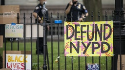 "MANHATTAN, NY - JUNE 30: Protesters signs hang on the gate in City Hall Park during the Occupy City Hall protests that say, ""Defund NYPD"" and ""BLM"" with NYPD police officers in the background. Earlier in the day, one of the members of Warriors in the Garden was beaten and arrested by police. This was part of the Occupy City Hall effort which has seen protesters camping out for days until today where New York City Council is to vote on the NYPD Budget. Protesters continue taking to the streets across America and around the world after the killing of George Floyd at the hands of a white police officer Derek Chauvin that was kneeling on his neck during for eight minutes, was caught on video and went viral. During his arrest as Floyd pleaded, ""I Can't Breathe"". The protest are attempting to give a voice to the need for human rights for African American's and to stop police brutality against people of color. They are also protesting deep-seated racism in America. Many people were wearing masks and observing social distancing due to the coronavirus pandemic. Photographed in the Manhattan Borough of New York on June 30, 2020, USA. (Photo by Ira L. Black/Corbis via Getty Images)"