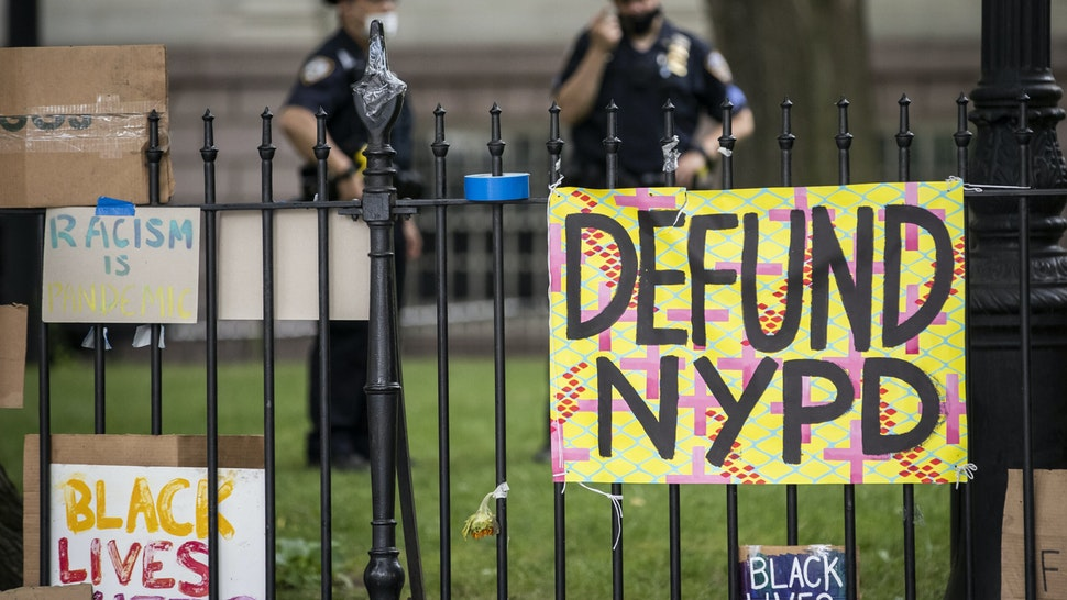 """MANHATTAN, NY - JUNE 30: Protesters signs hang on the gate in City Hall Park during the Occupy City Hall protests that say, """"Defund NYPD"""" and """"BLM"""" with NYPD police officers in the background. Earlier in the day, one of the members of Warriors in the Garden was beaten and arrested by police. This was part of the Occupy City Hall effort which has seen protesters camping out for days until today where New York City Council is to vote on the NYPD Budget. Protesters continue taking to the streets across America and around the world after the killing of George Floyd at the hands of a white police officer Derek Chauvin that was kneeling on his neck during for eight minutes, was caught on video and went viral. During his arrest as Floyd pleaded, """"I Can't Breathe"""". The protest are attempting to give a voice to the need for human rights for African American's and to stop police brutality against people of color. They are also protesting deep-seated racism in America. Many people were wearing masks and observing social distancing due to the coronavirus pandemic. Photographed in the Manhattan Borough of New York on June 30, 2020, USA. (Photo by Ira L. Black/Corbis via Getty Images)"""