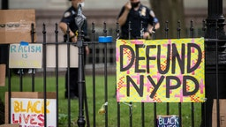 "Protesters signs hang on the gate in City Hall Park during the Occupy City Hall protests that say, ""Defund NYPD"" and ""BLM"" with NYPD police officers in the background."