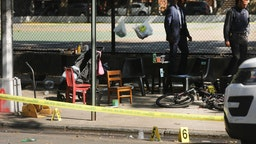 Police ballistic markers stand besides a child's chair and bicycle at a crime scene in Brooklyn where a one year old child was shot and killed on July 13, 2020 in New York City.