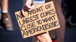 """A caucasian protester holds a sign that says, """"No Amount of Unrest Comes Close to What America Deserves"""" in Union Square Park, New York."""