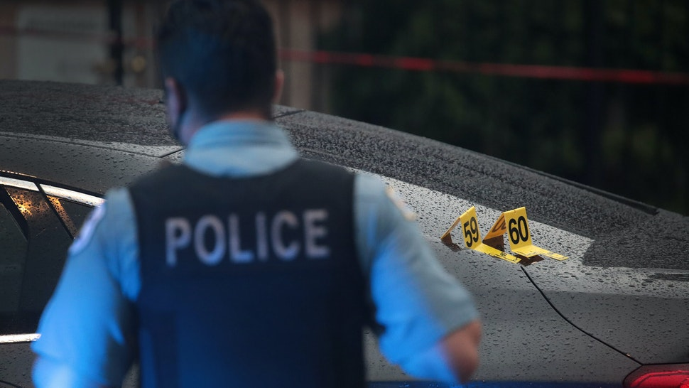 CHICAGO, ILLINOIS - JULY 21: Shell casings labeled 59 and 60 rest on a bullet-riddled car as police investigate the scene of a shooting in the Auburn Gresham neighborhood on July 21, 2020 in Chicago, Illinois. At least 14 people were transported to area hospitals after several gunmen, believed to be in the car, opened fire on mourners standing outside a funeral home. The car crashed and the occupants fled after mourners returned fire. More than 2000 people have been shot and more than 400 have been murdered in Chicago so far this year. (Photo by Scott Olson/Getty Images)