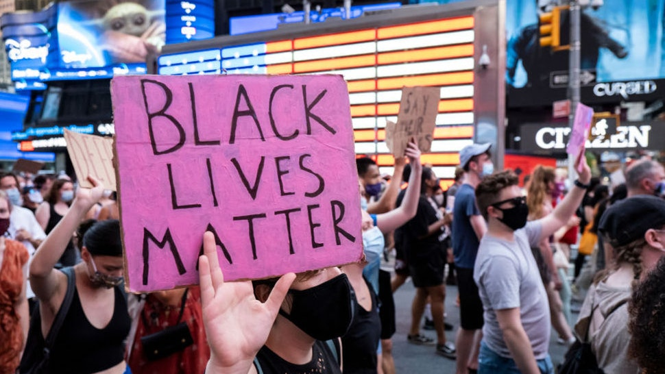 "A protester holds a sign that says, ""Black Lives Matter"" as the crowd of hundreds pass the Jumbotron of the American Flag in Times Square New York in support of Black Women."