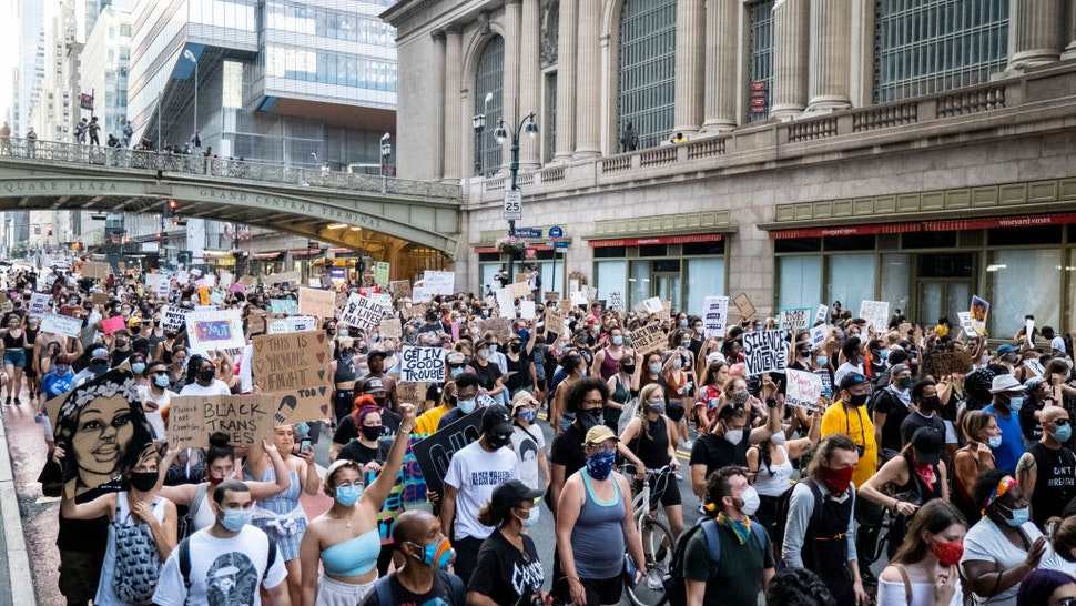 Hundreds of protesters carrying signs walk past Grand Central Station in Manhattan New York in support of Black Women.