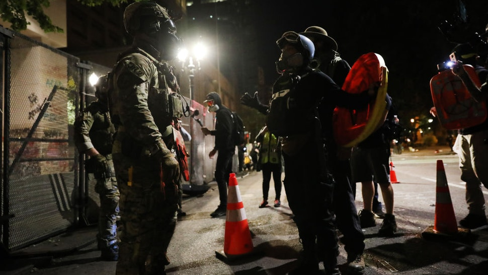 Federal police confront protesters in front of the Mark O. Hatfield federal courthouse in downtown Portland as the city experiences another night of unrest on July 26, 2020 in Portland, Oregon.