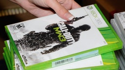 "NORTH LAS VEGAS, NV - NOVEMBER 08: GameStop employee Randi Taber rings up copies of ""Call of Duty: Modern Warfare 3"" for the Xbox 360 during a launch event for the highly anticipated video game at a GameStop Corp. store November 8, 2011 in North Las Vegas, Nevada. Video game publisher Activision released the eighth installment in the ""Call of Duty"" franchise at midnight. (Photo by Ethan Miller/Getty Images)"