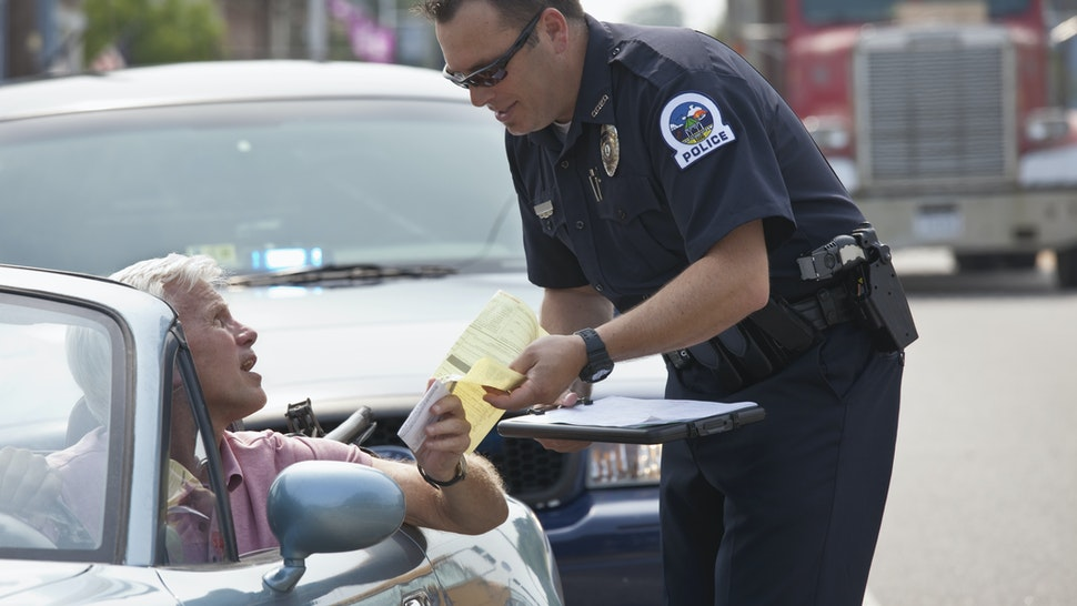 Policeman giving driver traffic citation - stock photo