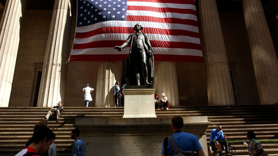 Pedestrians walk around the George Washington statue in front of Federal Hall September 5, 2002 in New York City.